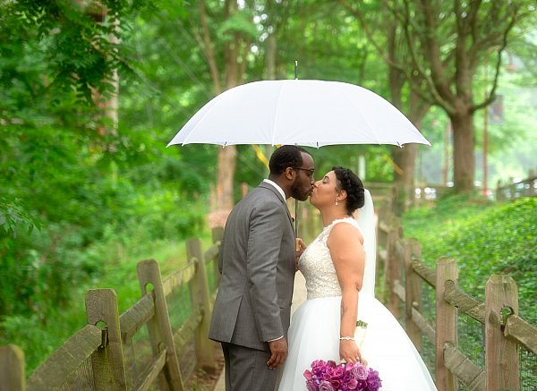Groom Kissing Bride Under White Umbrella